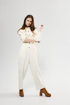 白いジャンプスーツのファッション服茶色の靴のきれいな女性。