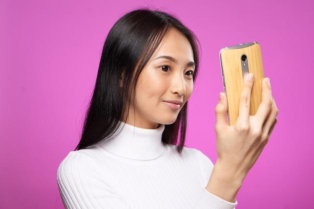 손 분홍색 배경 패션 커뮤니케이션에 흰색 스웨터 전화에 예쁜 여자