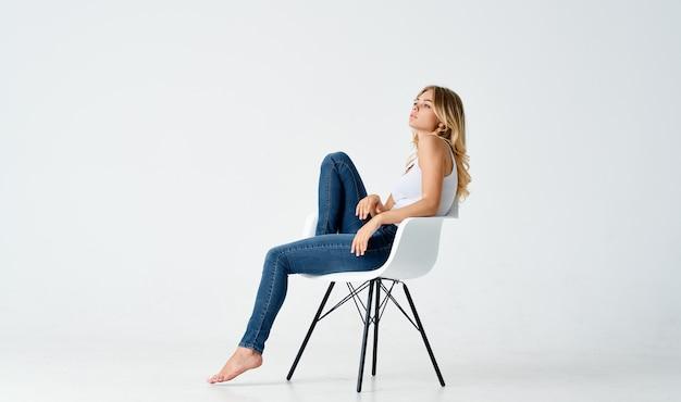 Красивая женщина в белой футболке и джинсах сидит на стуле с согнутыми ногами эмоции