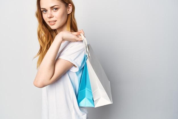 手に白いtシャツの買い物袋のきれいな女性