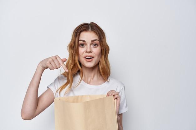 그녀의 손에 쇼핑백과 흰색 tshirt에 예쁜 여자