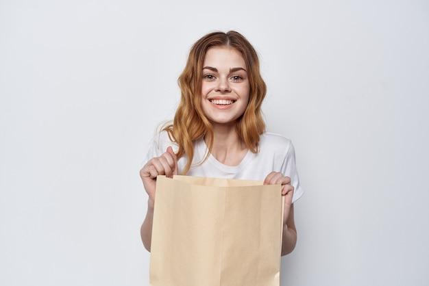 Красивая женщина в белой футболке с хозяйственной сумкой в руках