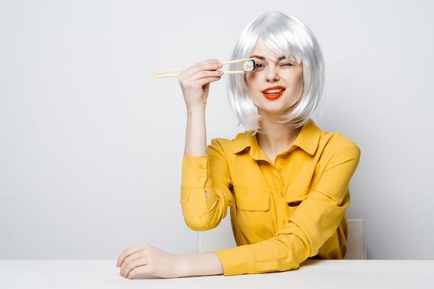Красивая женщина в белом парике ест суши-роллы