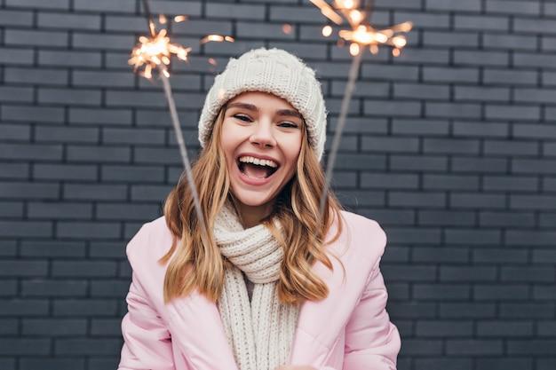 ポジティブな感情を表現し、線香花火を振る冬のアクセサリーのきれいな女性。新年を祝うピンクの帽子をかぶった素敵な女の子の屋外写真。