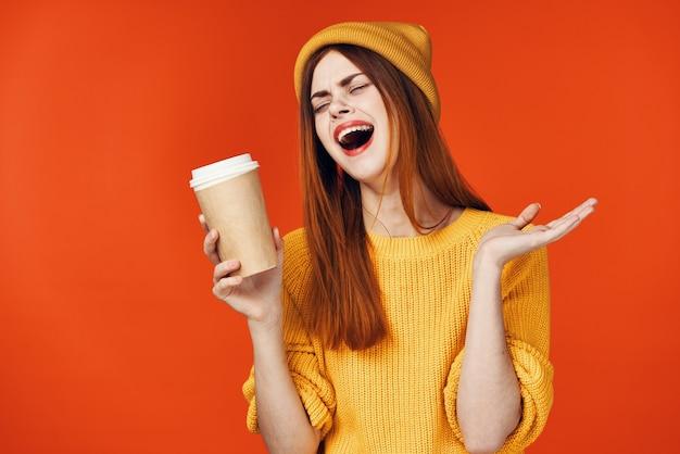 손 감정 고립 된 배경에 뜨거운 음료 한잔과 함께 노란색 모자에 예쁜 여자