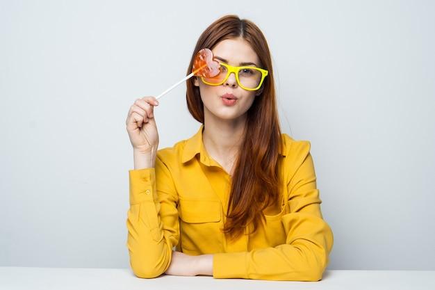 Красивая женщина в желтой рубашке сидит за столом в форме сердца на палочке