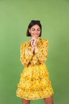 黄色い夏のドレスとサングラスを着たきれいな女性、緑のスタジオ、幸せなポジティブな陽気な喜びの感情