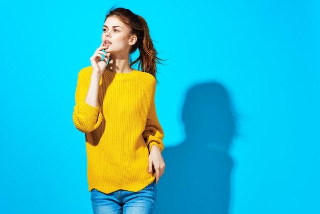 黄色いセーターの感情のきれいな女性は、スタジオブルーの手をジェスチャーします。