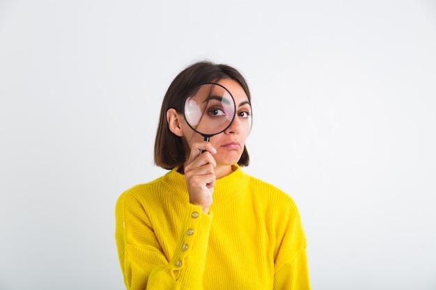 白地に黄色いセーターを着たきれいな女性が拡大鏡を保持している幸せな肯定的な遊び心