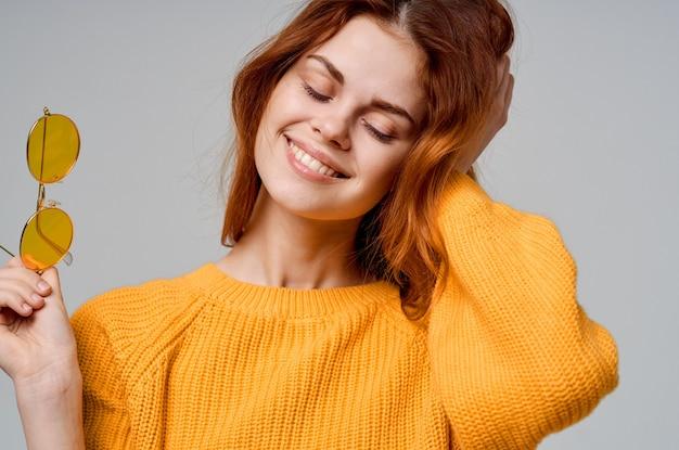 メガネスタジオファッションと黄色のセーターのきれいな女性