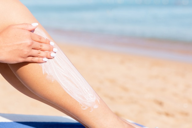 Pretty woman is applying sun cream on her leg with her hand relaxing on the sunbed by the sea