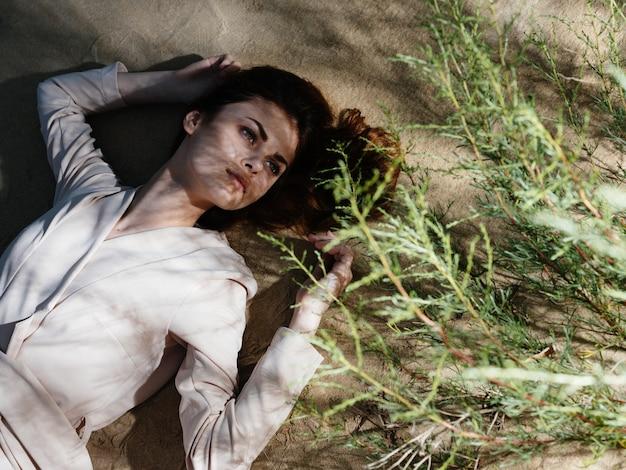 Красивая женщина лежит на песке земли