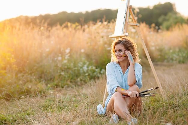 きれいな女性が絵を描いています。オープンエアセッション。かわいい女性は日没時に絵を描きます。ガールアーティスト Premium写真