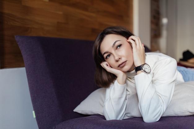 きれいな女性は仕事の後自宅のベッドでリラックス