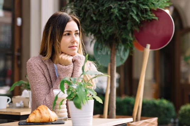 예쁜 여자는 따뜻한 스웨터를 입은 카페테리아에 앉아 누군가를 기다리고 있습니다. 그녀는 옆으로 찾고 있습니다. 그녀는 따뜻한 음료로 몸을 따뜻하게합니다. 가을 날, 외부 초상화, 회의.