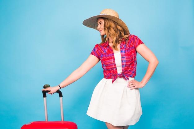 きれいな女性が赤いスーツケースに座っています。美容、ファッション、旅行、人々のコンセプト。