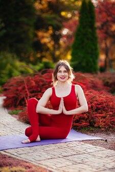 Красивая женщина носит спортивную одежду, делает упражнения йоги в парке.
