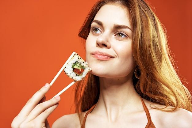 きれいな女性の日本の箸寿司ロールダイエット感情。