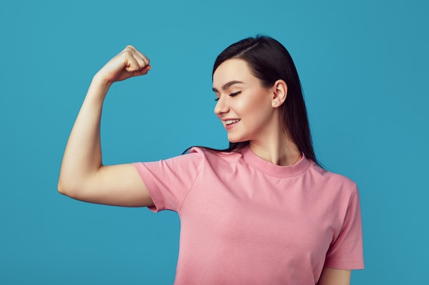 Pretty woman keeps fit and healthy raises hand and shows muscles