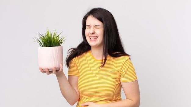Красивая женщина громко смеется над веселой шуткой и держит декоративное растение