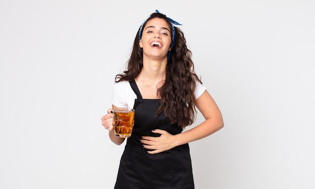 Красивая женщина громко смеется над какой-то веселой шуткой и держит пинту пива