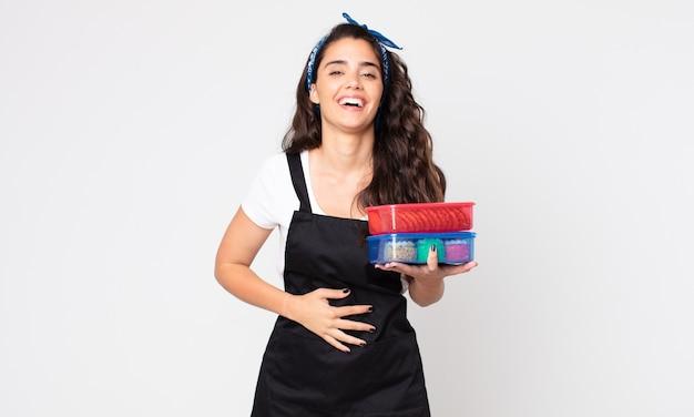 Красивая женщина громко смеется над какой-то веселой шуткой и держит посуду с едой