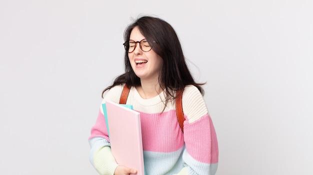 いくつかの陽気な冗談で大声で笑っているきれいな女性。大学生のコンセプト