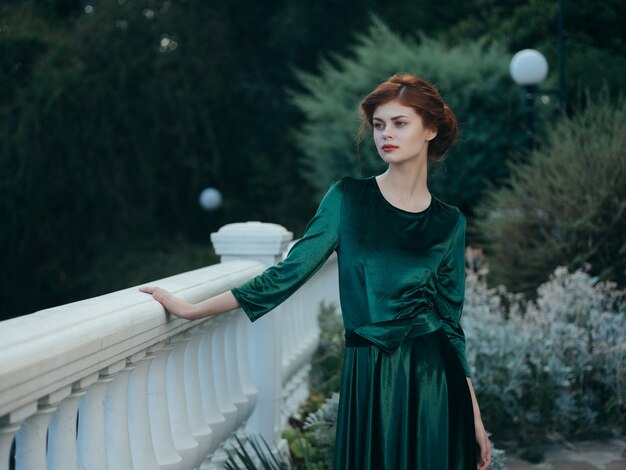 緑のドレスパークウォークで手すりに寄りかかってきれいな女性