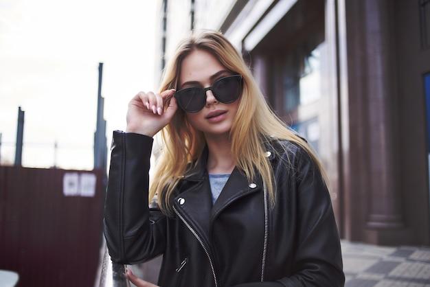 Pretty woman in leather jacket walking down the street