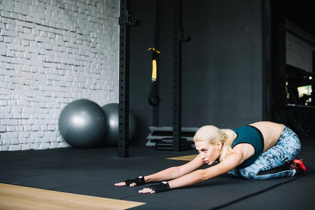 Pretty woman in leggings stretching