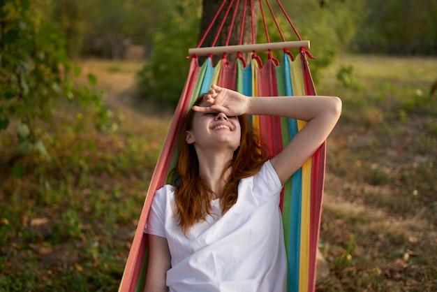 きれいな女性はハンモック屋外自然の木に横たわっています