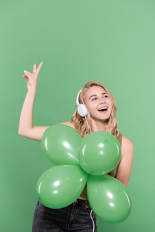 Pretty woman listening to music and holding balloons