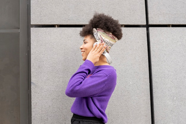 Pretty woman listening to music on the street with headphones and smarpthone