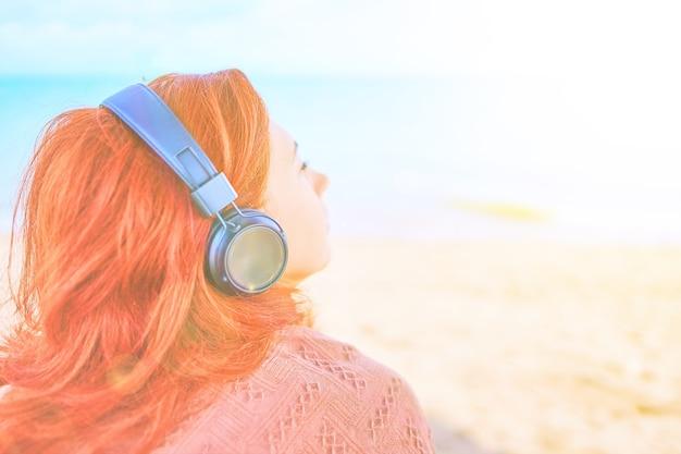 ビーチで音楽を聴いているきれいな女性赤毛の女の子がリスニングデバイスでメロディーを聴いています...