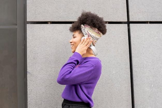 ヘッドフォンとsmarpthoneで路上で音楽を聴いているきれいな女性
