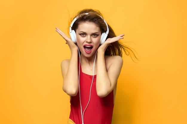 Красивая женщина слушает музыку в наушниках весело желтый фон
