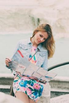 Красивая женщина ищет туристическую карту возле фонтана треви