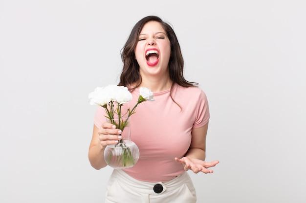 Красивая женщина выглядит сердитой, раздраженной и разочарованной и держит в руках декоративный цветочный горшок
