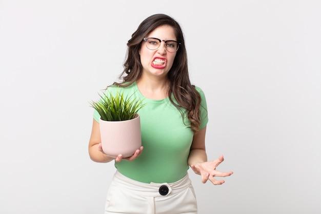 Красивая женщина выглядит сердитой, раздраженной и разочарованной и держит декоративное растение