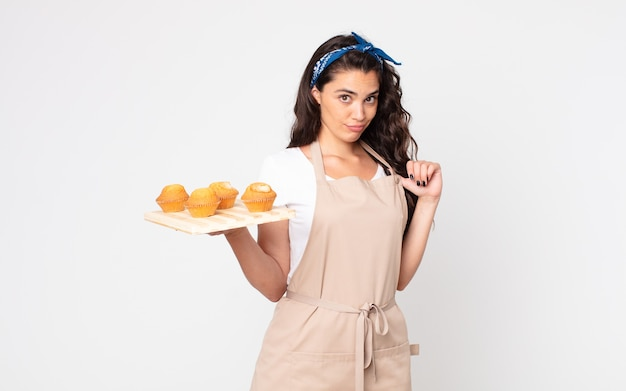 Pretty woman looking arrogant, successful, positive and proud and holding a muffins tray