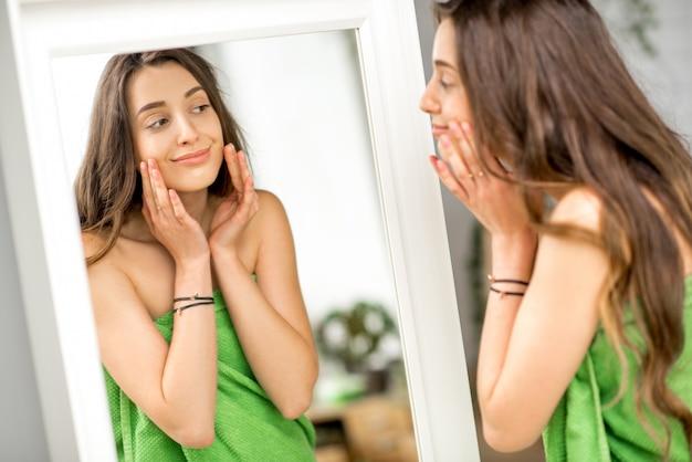 화장실에서 수건에 서 있는 미소로 거울을 보고 있는 예쁜 여자