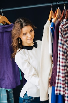 Pretty woman looking at clothes on rack