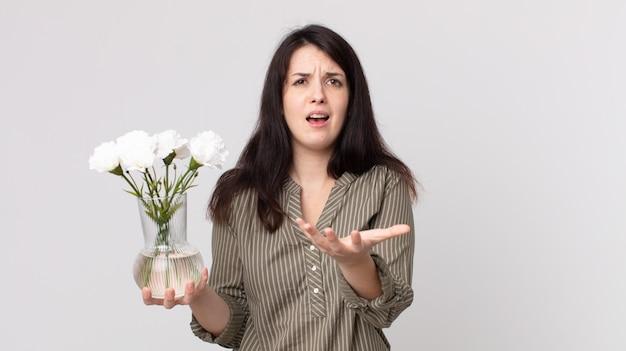 Красивая женщина выглядит отчаянно, разочарованно и подчеркнуто и держит декоративные цветы. помощник агента с гарнитурой