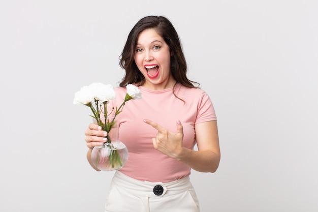 Красивая женщина выглядит взволнованной и удивленной, указывая в сторону и держа декоративный горшок с цветами