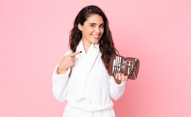 Красивая женщина выглядит взволнованной и удивленной, указывая в сторону и держа сумку для макияжа с инструментами для ногтей