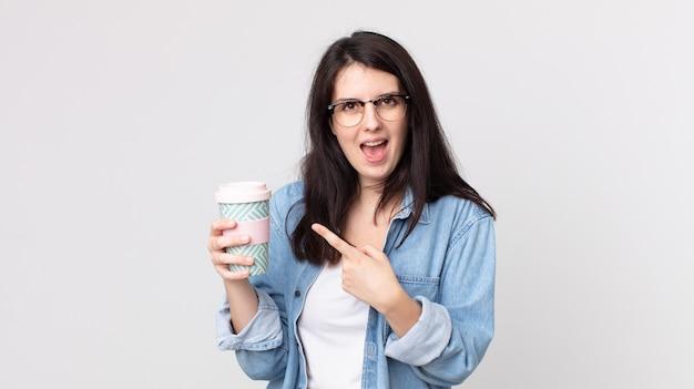 Красивая женщина выглядит взволнованной и удивленной, указывая в сторону и держа кофе на вынос