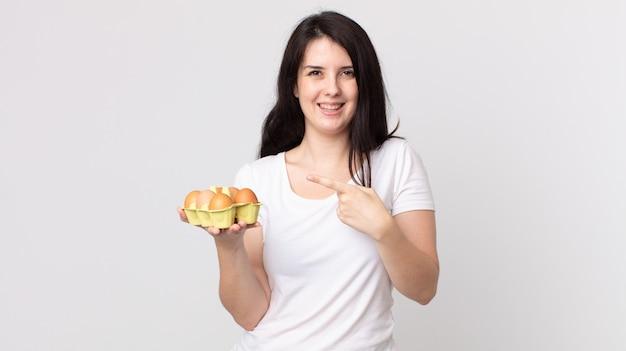 Красивая женщина выглядит взволнованной и удивленной, указывая в сторону и держа коробку для яиц