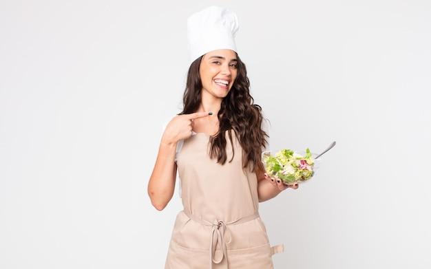 Красивая женщина выглядит взволнованной и удивленной, указывая в сторону в фартуке и держа салат