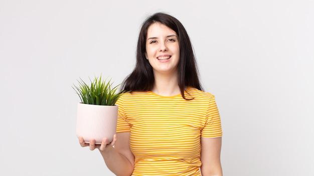 Красивая женщина выглядит счастливой и приятно удивленной и держит декоративное растение
