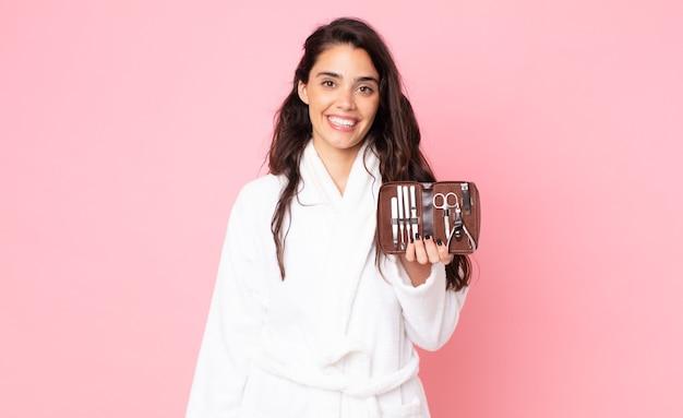 Красивая женщина выглядит счастливой и приятно удивленной и держит сумку для макияжа с инструментами для ногтей